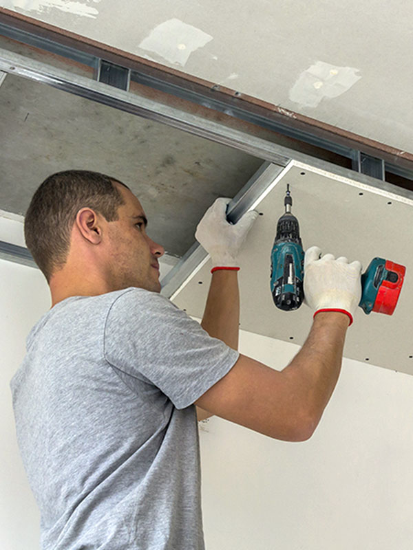 Man placing ceiling tiles during building construction